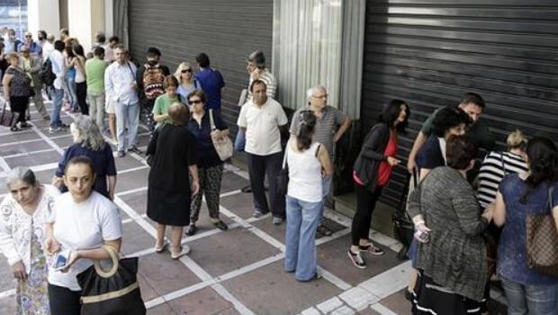 Imagen de personas esperando en la puerta de una entidad financiera en el corralito griego de 2015