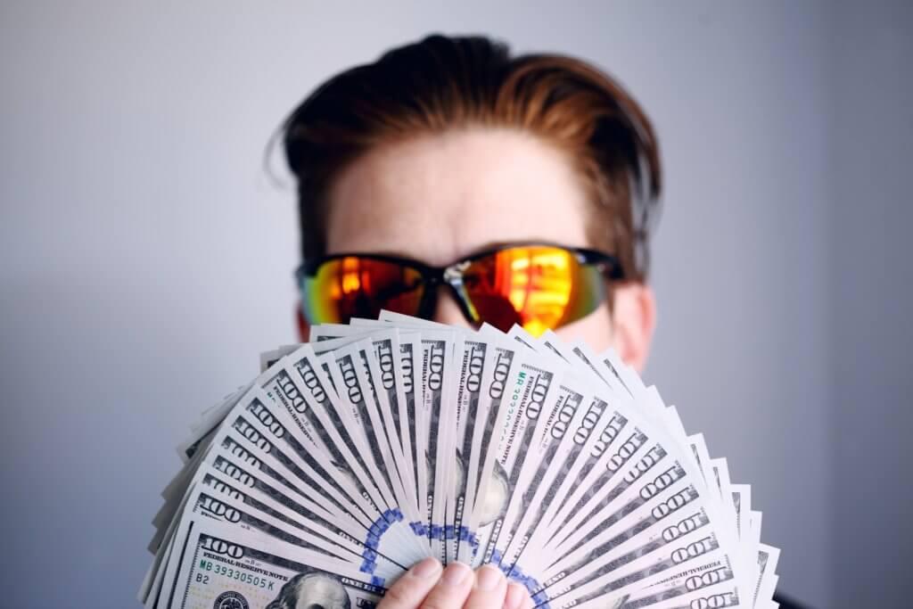 Imagen de un chico con un fajo de billetes en las manos